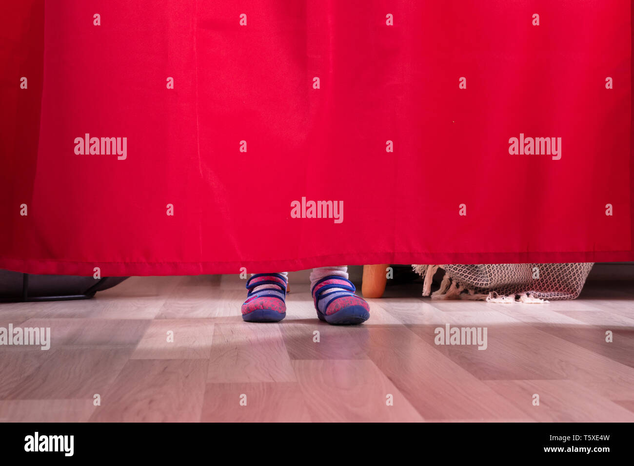 Low Section Of A Girl's Feet Behind The Curtain On Hardwood Floor - Stock Image