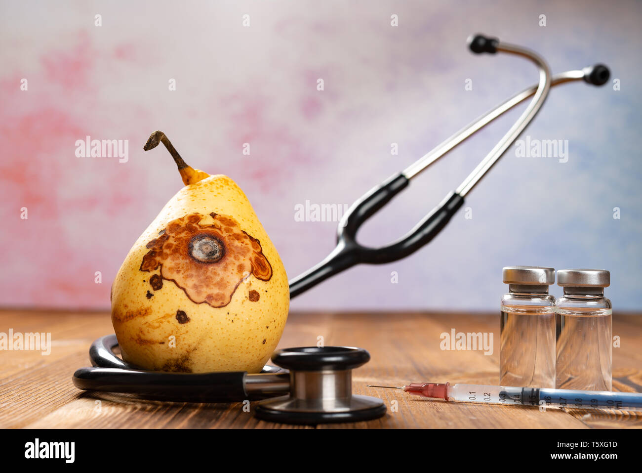 rotten pear surrounded by stethoscope - Stock Image