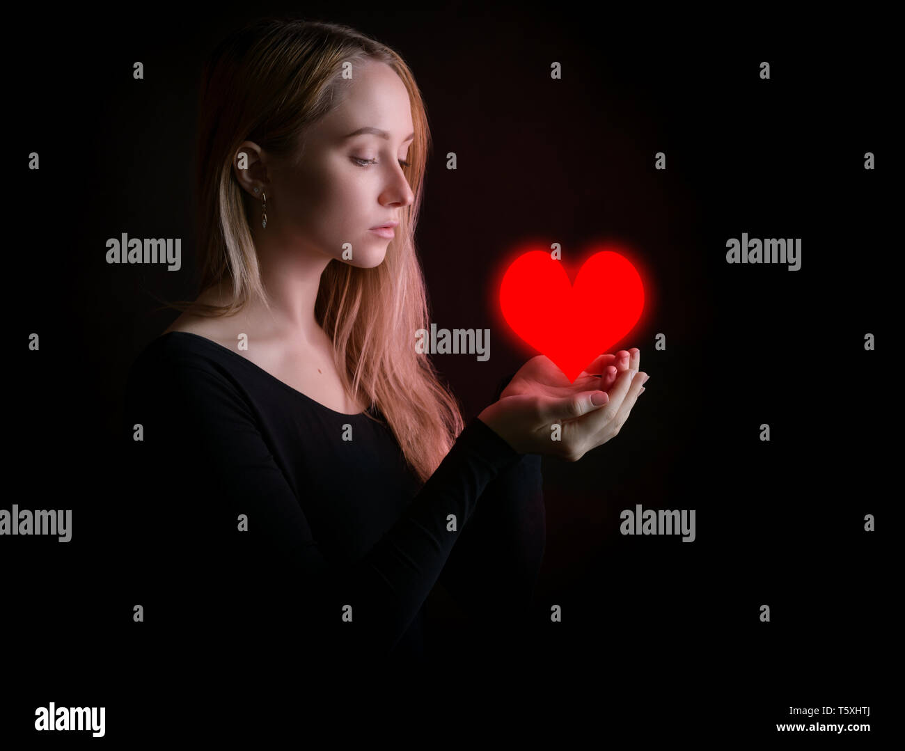 Sad young woman hold red heart on dark background. - Stock Image