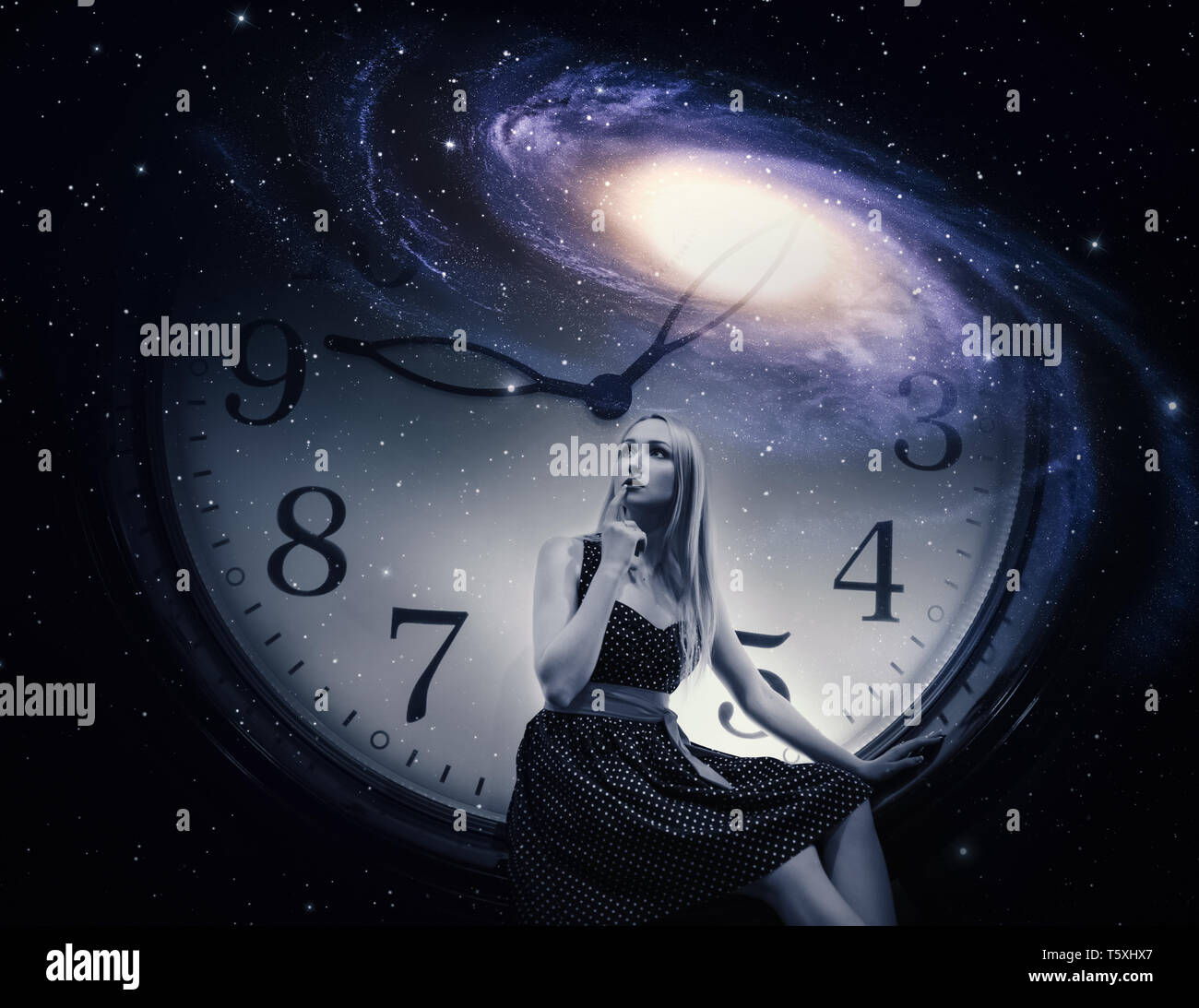 Young woman dressed in a dress with giant clock and galaxy. Time concept. Stock Photo