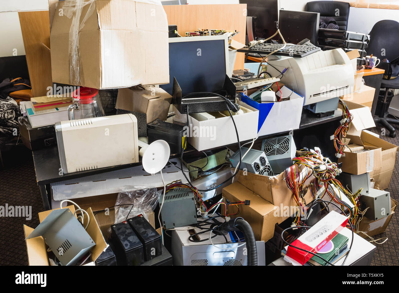 A messy desktop with stacks of files and other documents, all kind of office supplies and part of a keyboard. - Stock Image