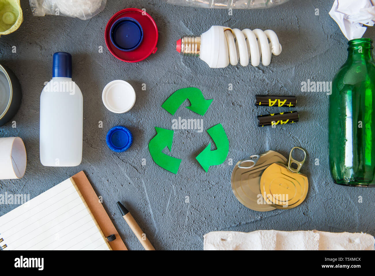 Recycling. Green recycle eco symbol. Recycled arrows sign near matherials for recycle and reuse on dark stone background top view - Stock Image
