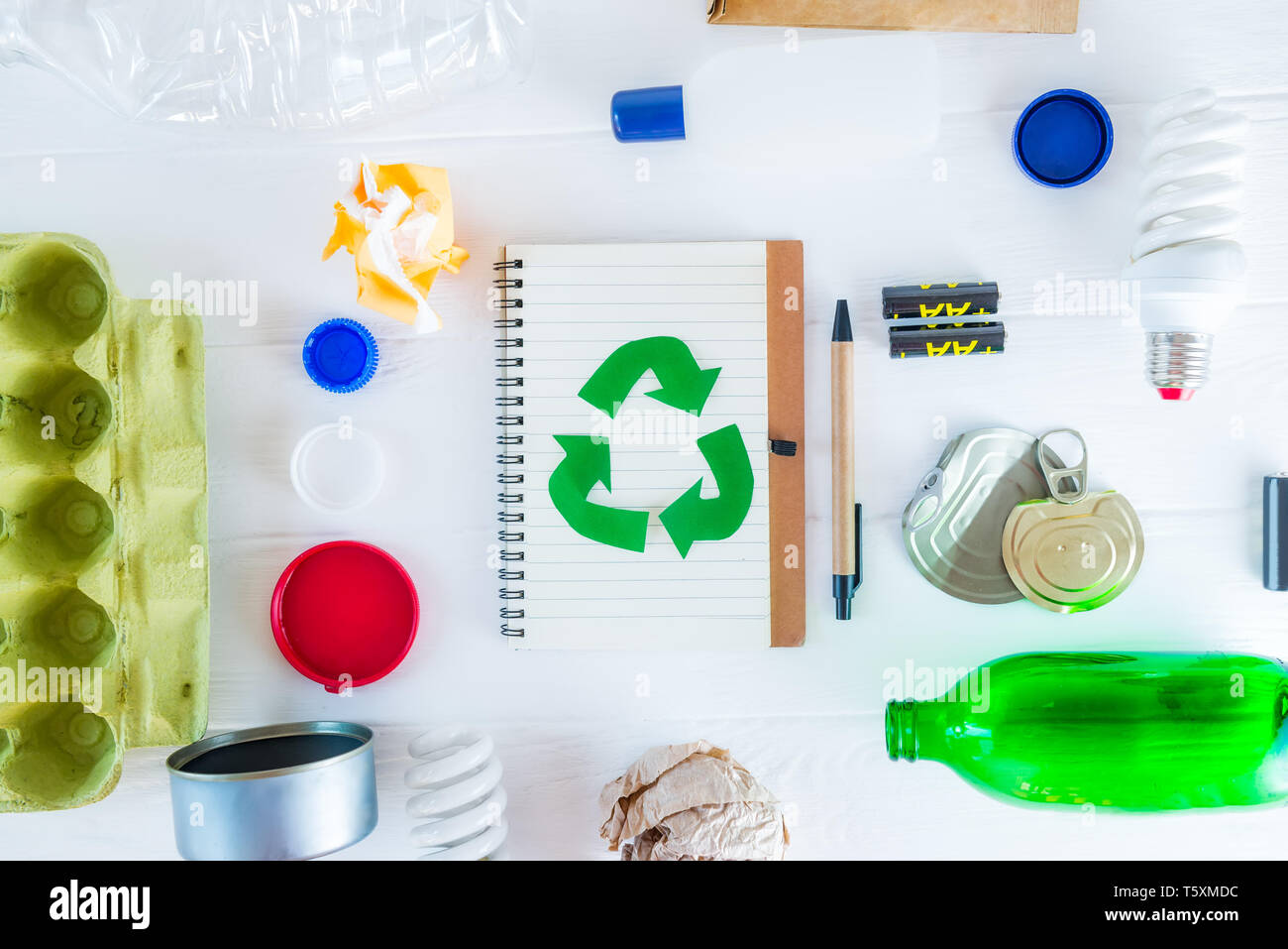 Top view recycle paper notebook with Green eco symbol surrounded with non recycling garbage and reusable waste as metal, plastic, old paper, glass pro - Stock Image