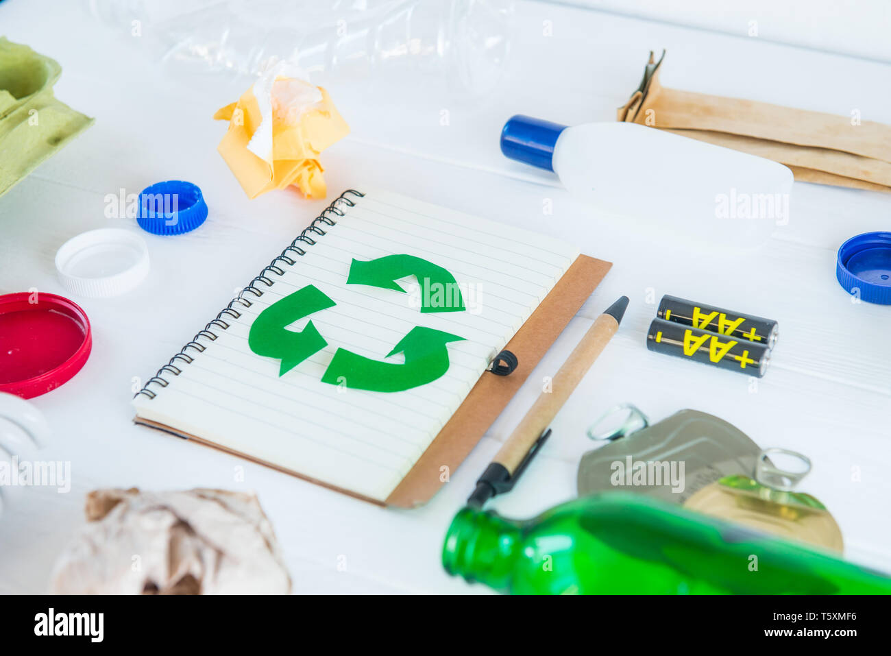 Recycle paper notebook with Green eco symbol surrounded with non recycling garbage and reusable waste as metal, plastic, old paper, glass products on  - Stock Image