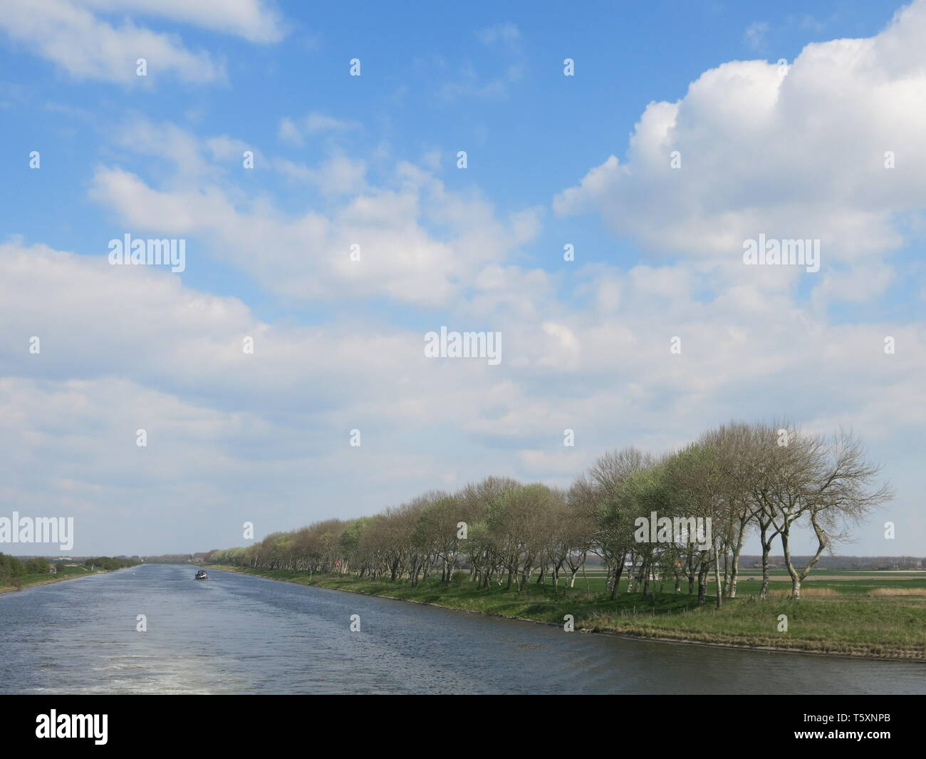 Cruising the waterways of the Netherlands is a peaceful way to explore the wide, flat canal and river landscape, and big, big skies - Stock Image