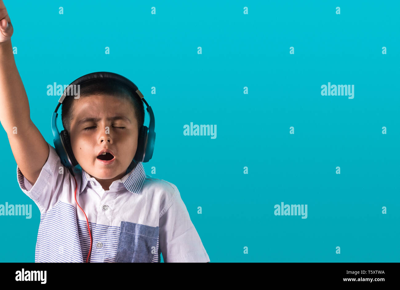 Small boy with expressive face listening to music on headphones dancing and singing authentic unposed image with copy space for text. - Stock Image