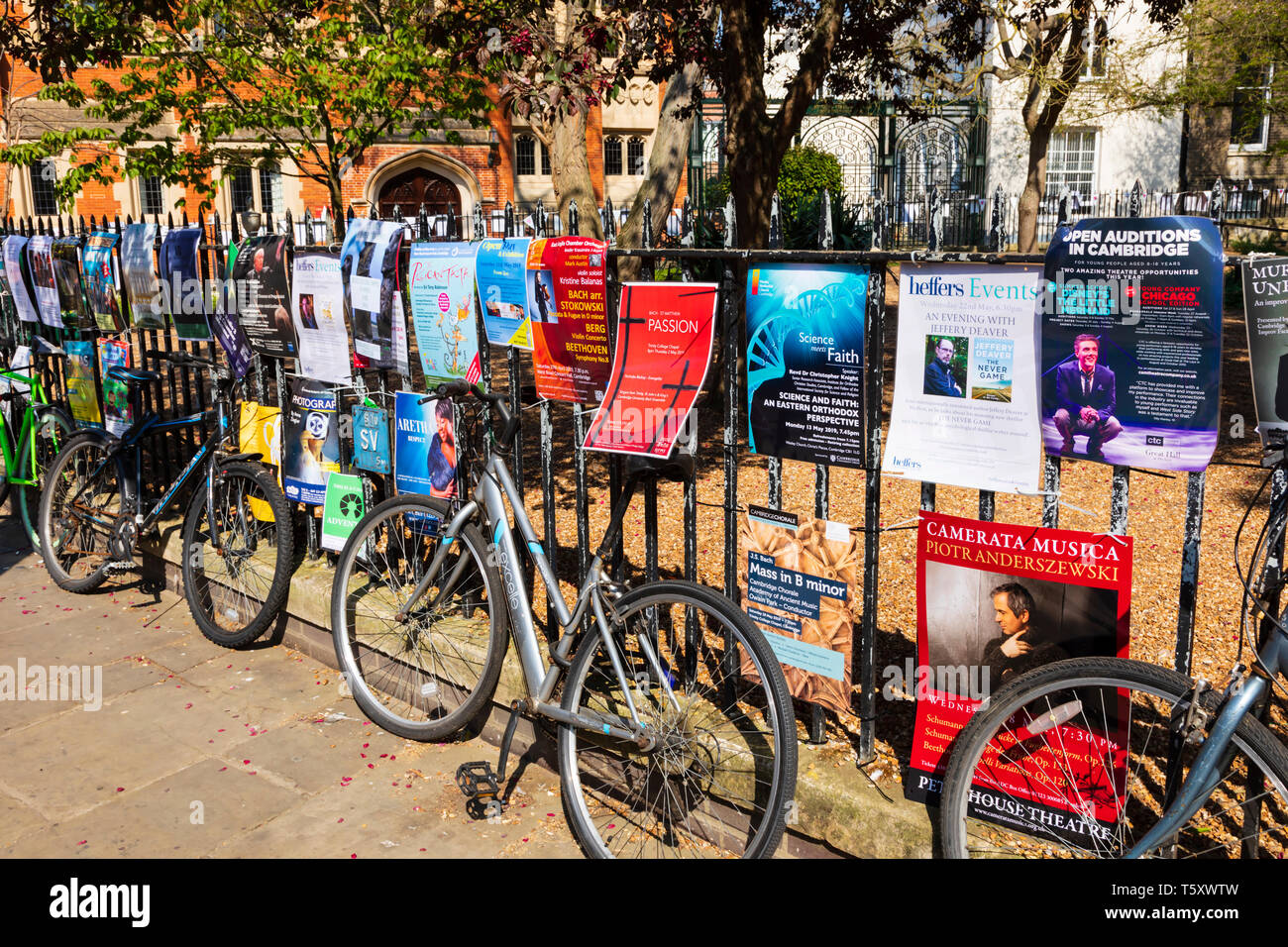 Bicycles and posters on the railings of the All Saints garden, art and craft fair, Trinity Street, University town of Cambridge, Cambridgeshire, Engla - Stock Image