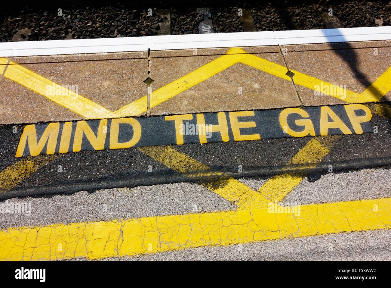 'Mind the gap' warning sign on the railway platform edge. - Stock Image