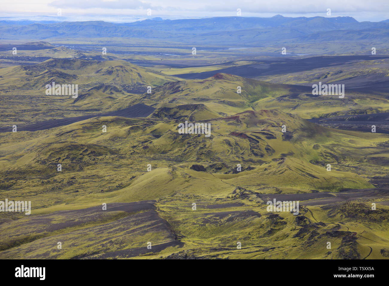 Dramatic iceland landscape of Craters of Laki volcanic fissure with a green hill and black lava looks like a moon - Stock Image