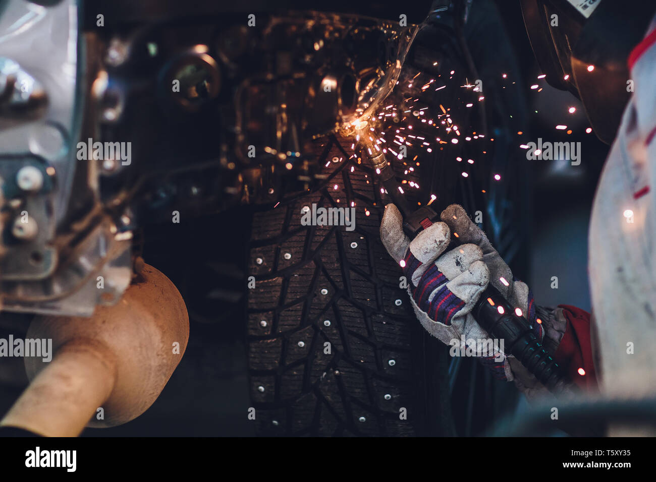 professional repairman worker in automotive industry welding metal body car with sparks. Stock Photo