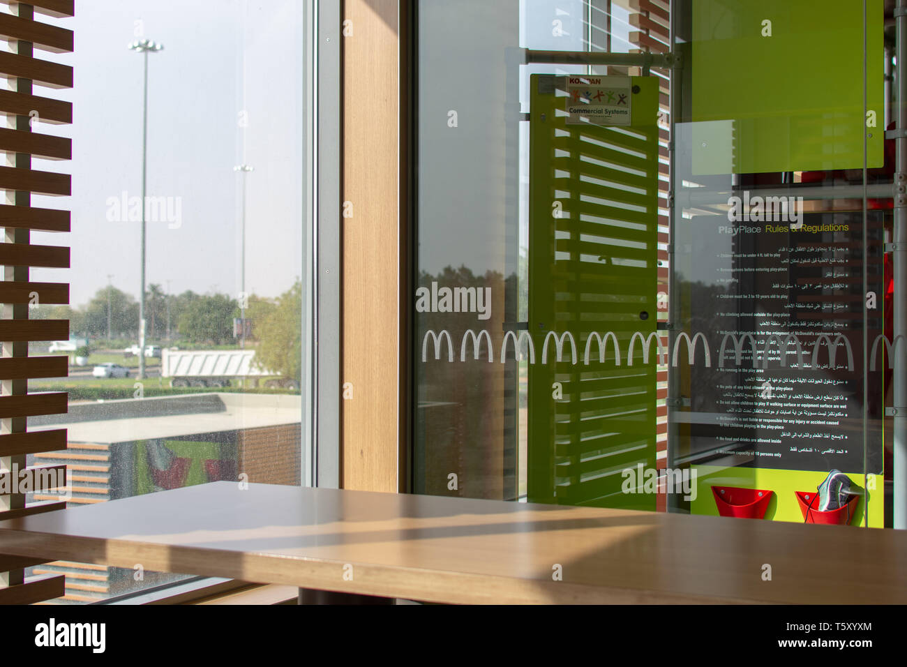 'Al Ain, Abu Dhabi/United Arab Emirates - 4/3/2019 - McDonalds Golden Arches Logo on glass by a play place or playground in an empty restaurant lookin - Stock Image