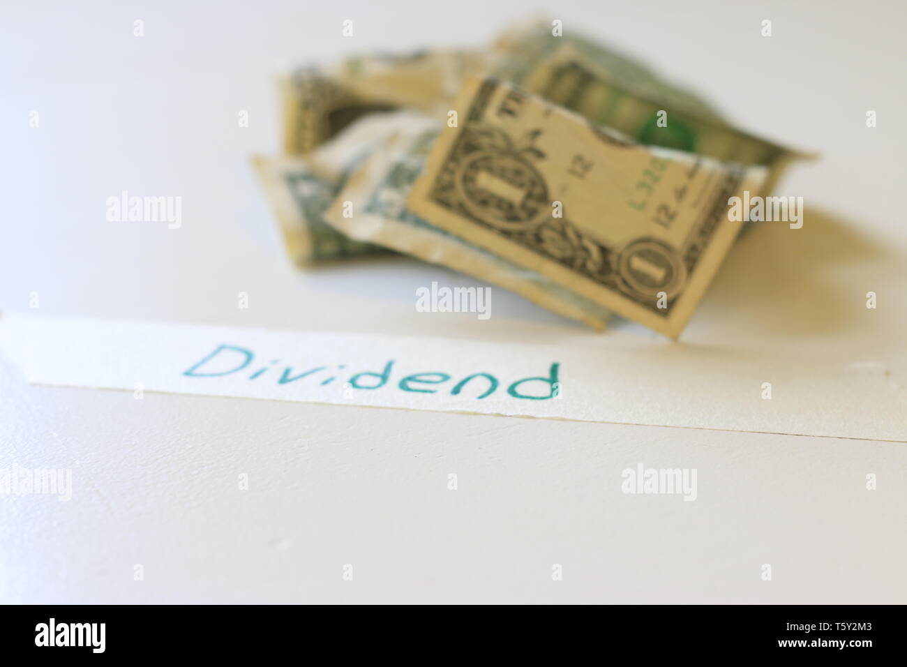 The word dividend next to US 1 dollar bills. Concept of dividend payments and stocks - Stock Image