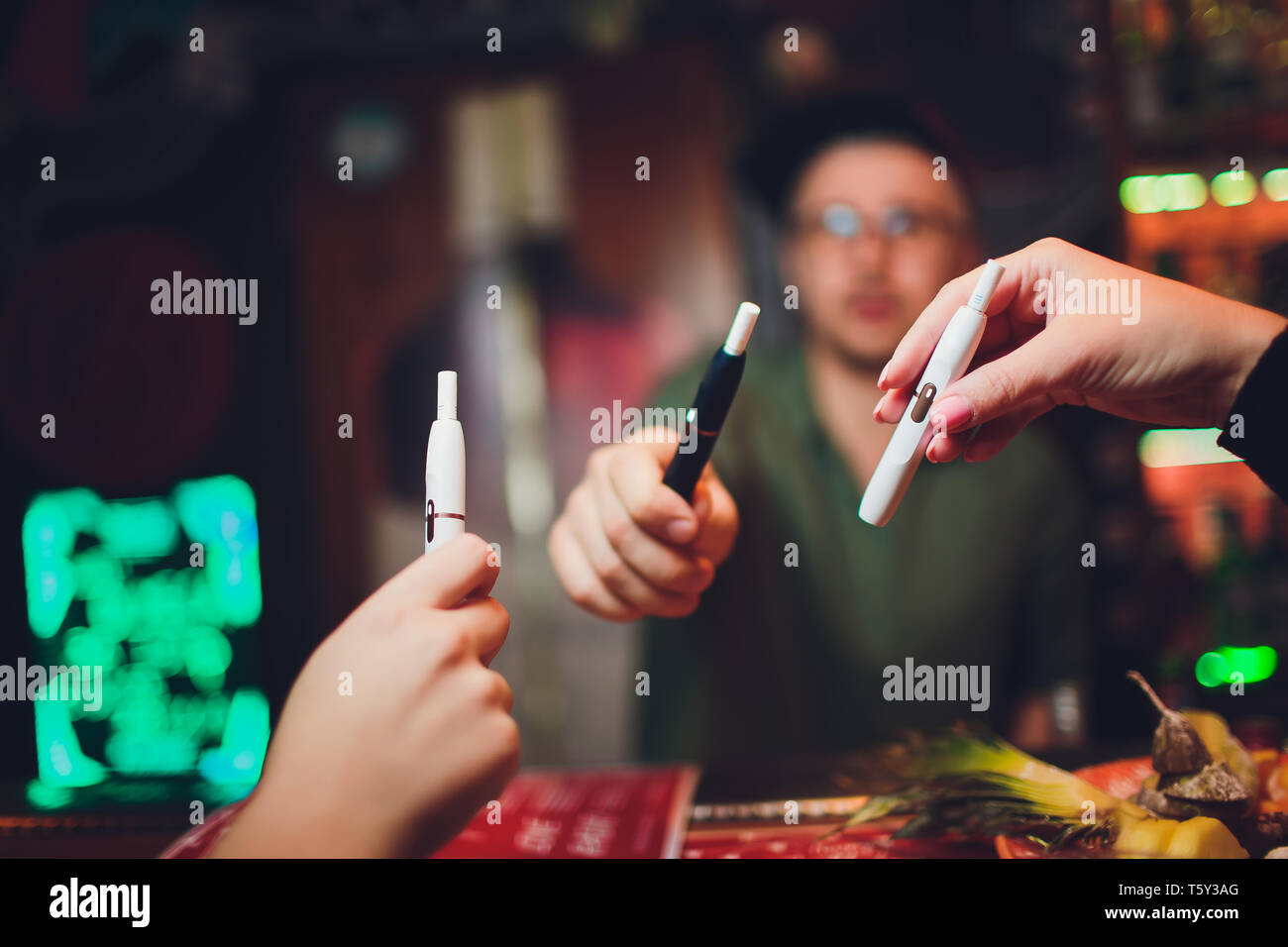 IQOS heat-not-burn tobacco product technology. Woman holding e-cigarette in his hand before smoking. - Stock Image