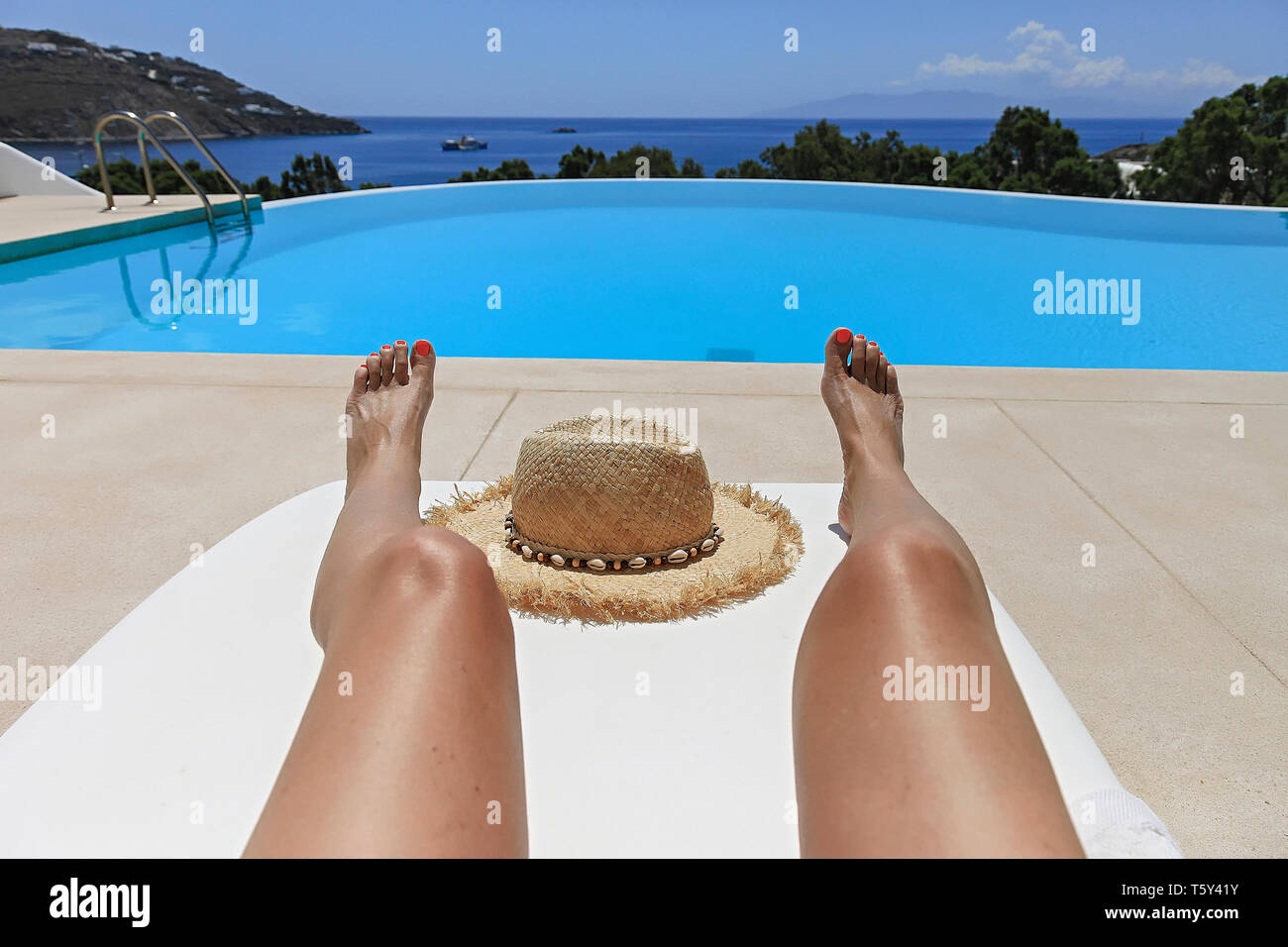 Female Legs Sunbathing On Patio Chaise Lounge Chair Near