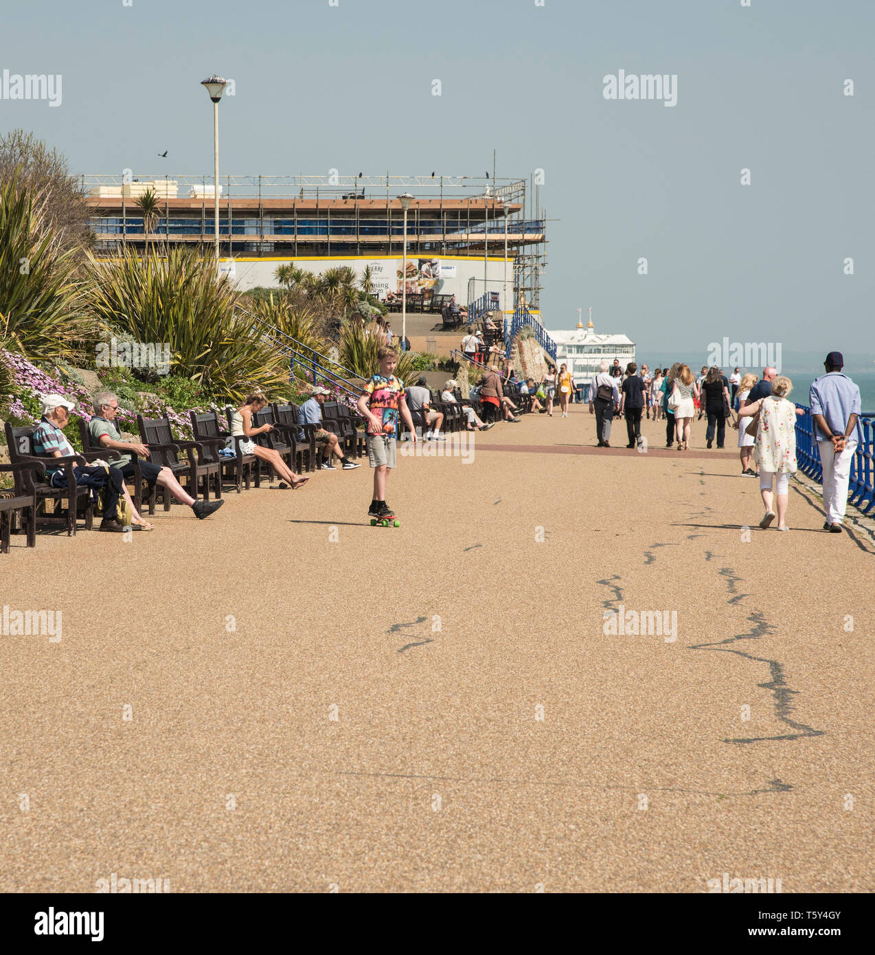 Many people casually walking and relaxing along the promenade on the East Sussex coast of Eastbourne  England UK - Stock Image