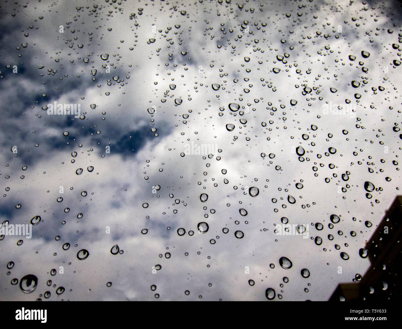 droppletdrops of water on glass reflecting the clouds - Stock Image