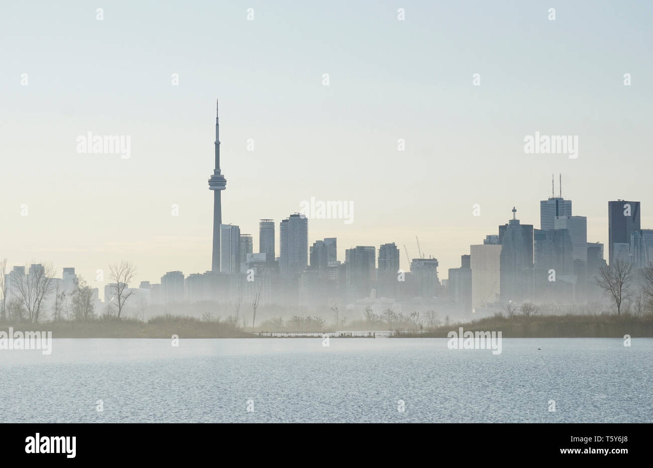 Sihouettes of Toronto waterfront landmark buildings in foggy haze in a warm spring day Stock Photo