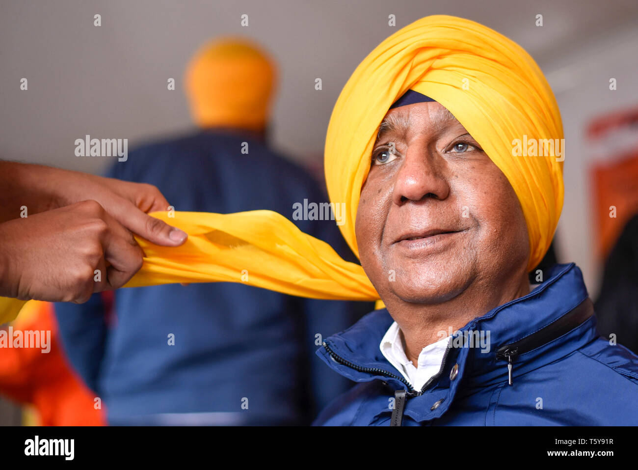 London, UK.  27 April 2019.  A man has a turban tied during the festival of Vaisakhi in Trafalgar Square, hosted by the Mayor of London.  For Sikhs and Punjabis, the festival celebrates the spring harvest and commemorates the founding of the Khalsa community over 300 years ago.  Credit: Stephen Chung / Alamy Live News - Stock Image