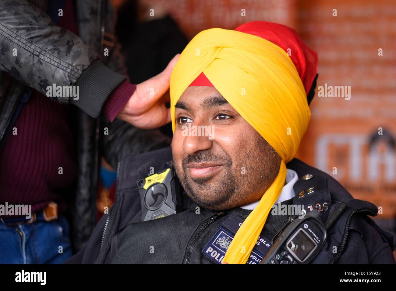 London, UK.  27 April 2019.  A police officer has a turban tied during the festival of Vaisakhi in Trafalgar Square, hosted by the Mayor of London.  For Sikhs and Punjabis, the festival celebrates the spring harvest and commemorates the founding of the Khalsa community over 300 years ago.  Credit: Stephen Chung / Alamy Live News - Stock Image