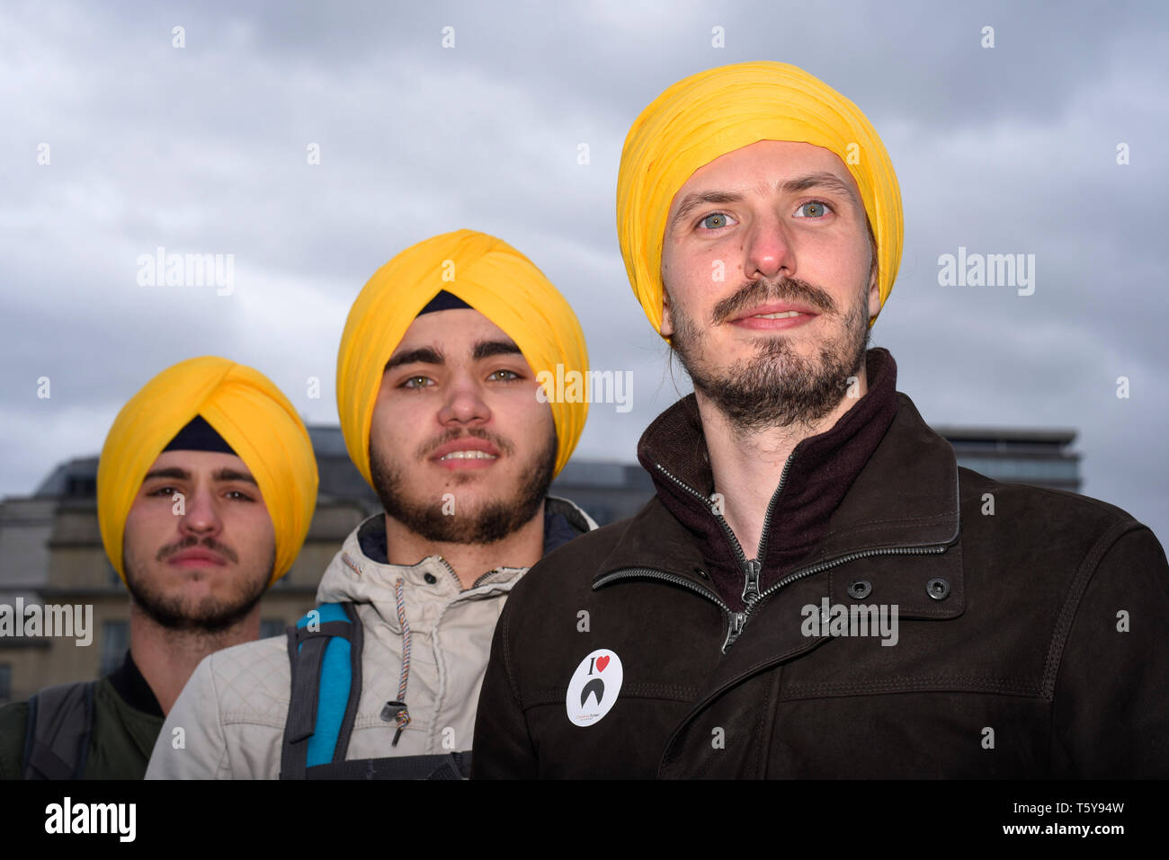 London, UK.  27 April 2019. Rares, Razvan and Artur, tourists from Romania, join in the festivities wearing turbans during the festival of Vaisakhi in Trafalgar Square, hosted by the Mayor of London.  For Sikhs and Punjabis, the festival celebrates the spring harvest and commemorates the founding of the Khalsa community over 300 years ago.  Credit: Stephen Chung / Alamy Live News - Stock Image