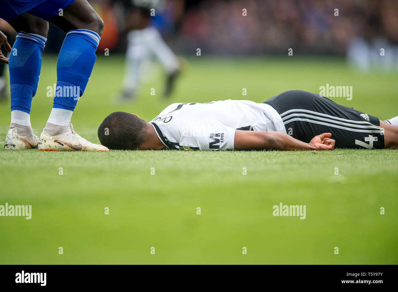 Craven Cottage, London, England, UK. 27th April 2019.  Denis Odoi of Fulham lies unconscious on the ground after a collision during the Premier League match between Fulham and Cardiff City at Craven Cottage, London, England on 27 April 2019. Photo by Salvio Calabrese.  Editorial use only, license required for commercial use. No use in betting, games or a single club/league/player publications. - Stock Image