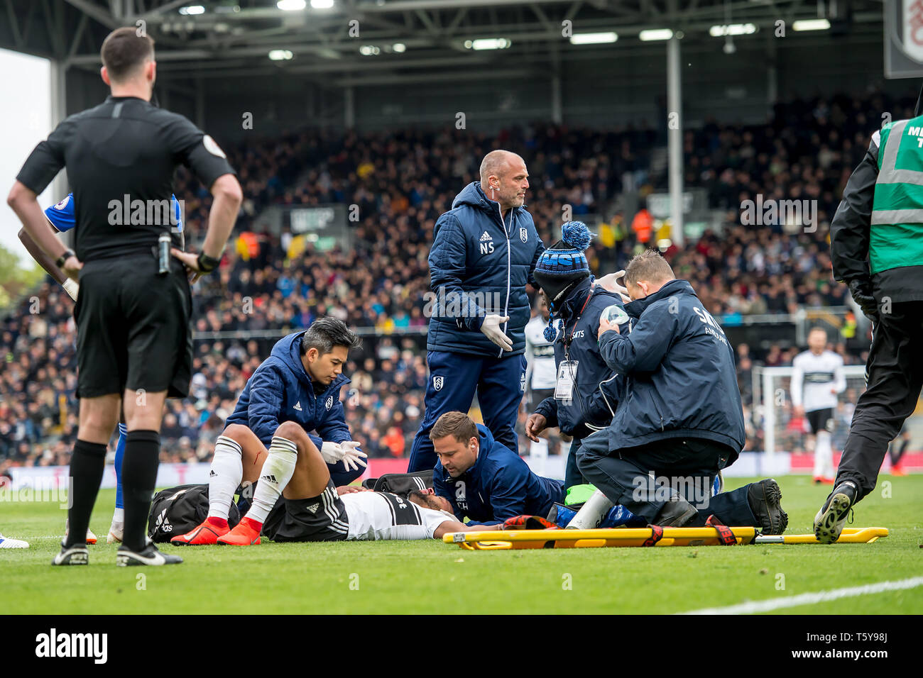 Craven Cottage, London, England, UK. 27th April 2019.  Denis Odoi of Fulham lies on the ground with blood on his face and receives medical attention during the Premier League match between Fulham and Cardiff City at Craven Cottage, London, England on 27 April 2019. Photo by Salvio Calabrese.  Editorial use only, license required for commercial use. No use in betting, games or a single club/league/player publications. - Stock Image