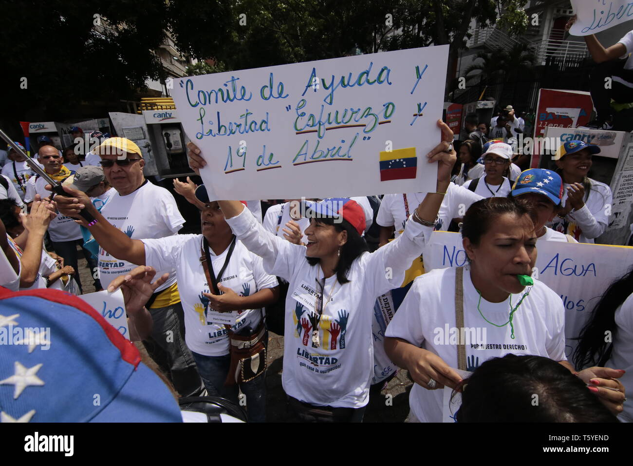 Caracas, Venezuela. 27th Apr, 2019. A woman is holding a banner with the inscription 'Comite de ayuda y libertad, esfuerzo y 19 de abril' at a public rally called by Venezuela's self-proclaimed president, Guaido. The Venezuelan opposition joins efforts to secure a major national march in Caracas on 1 May. Credit: Angel Hernandez/dpa/Alamy Live News - Stock Image