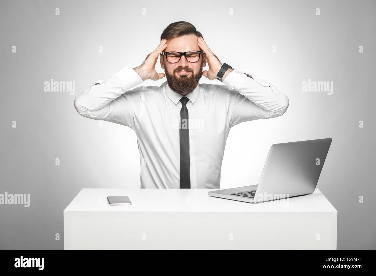 Headache. Portrait of unhealphy painful young manager in white shirt and black tie are sitting in office and have strong headache, holding fingers nea - Stock Image