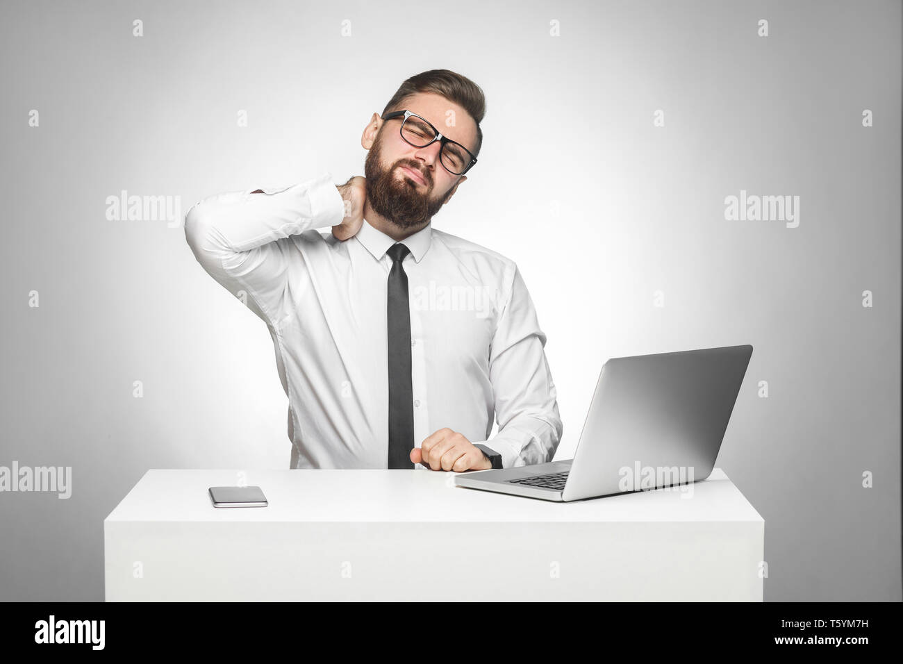 Portrait of unhealphy upset tired young boss in white shirt and black tie are sitting in office and have strong pain in neck, holding hand on neck. St - Stock Image