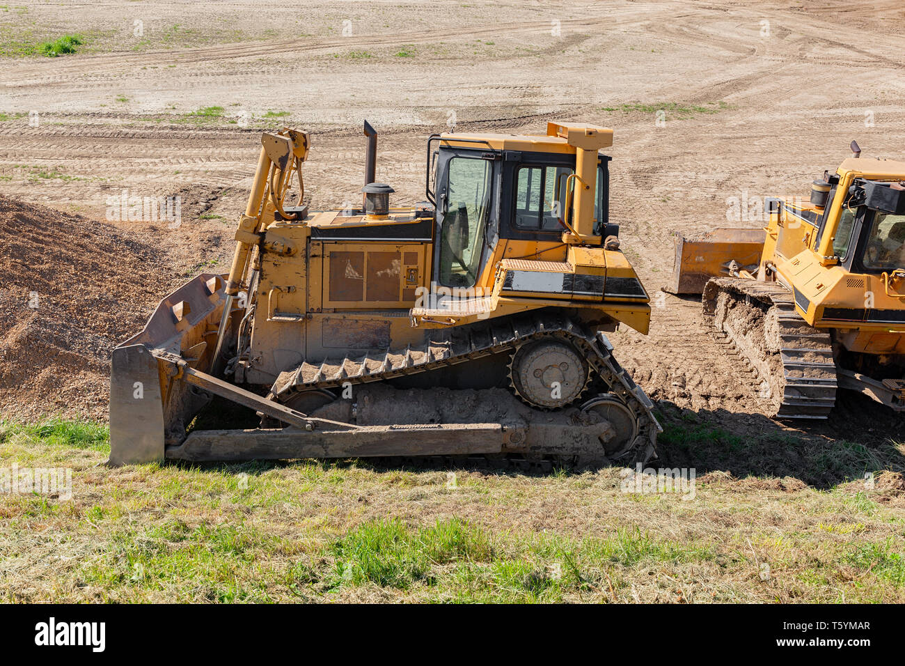 Yellow dozer on a dirt terrain with small patches of green grass - Stock Image