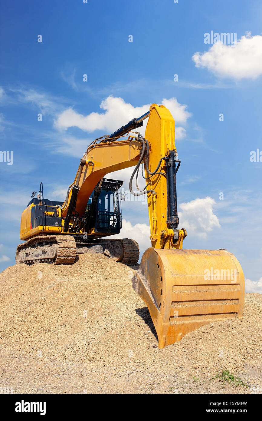Yellow excavator on a pile of dirt with blue sky with white clouds in the background - Stock Image