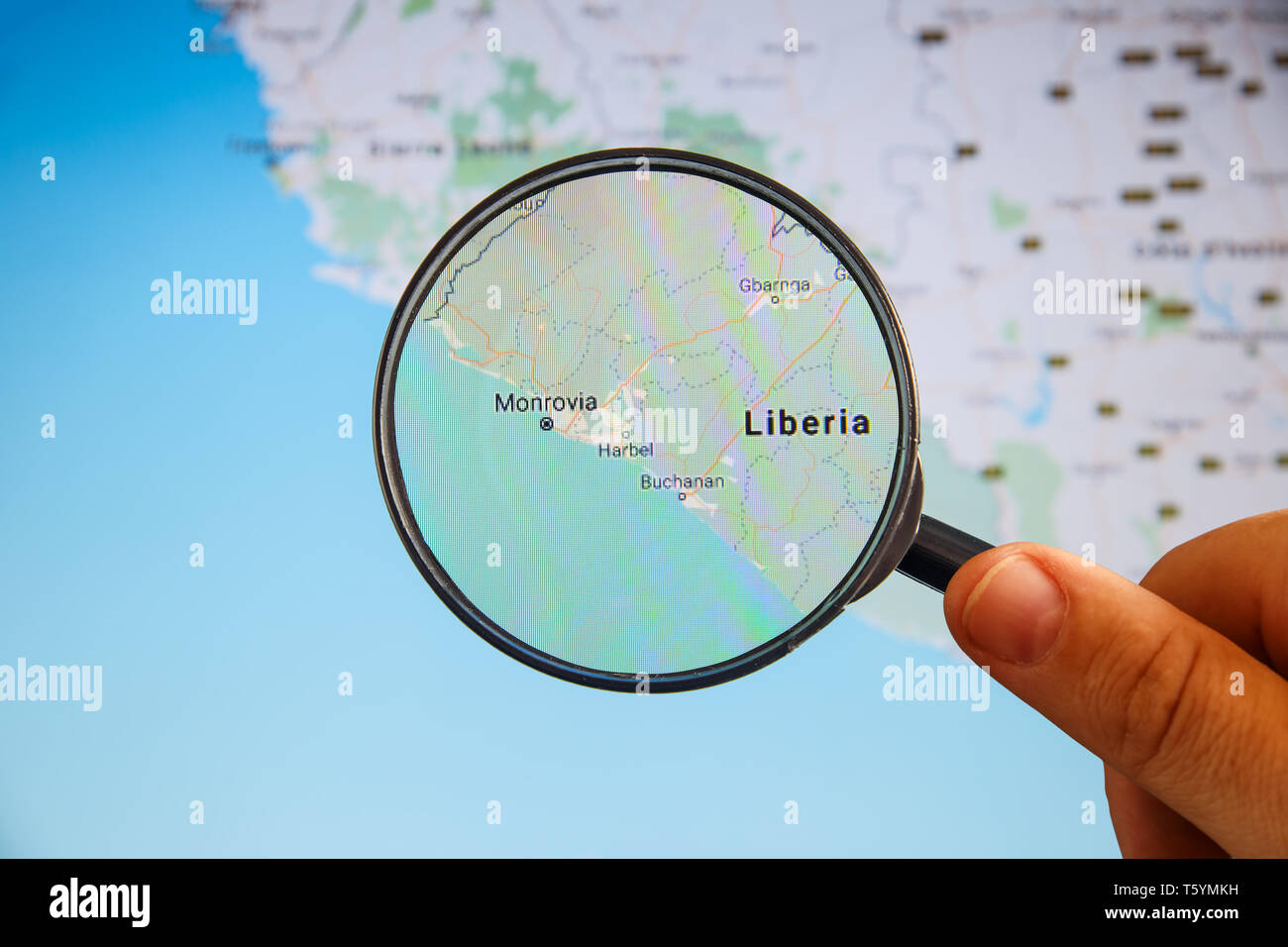 Monrovia, Liberia. Political map. City visualization illustrative concept on display screen through magnifying glass in the hand. - Stock Image