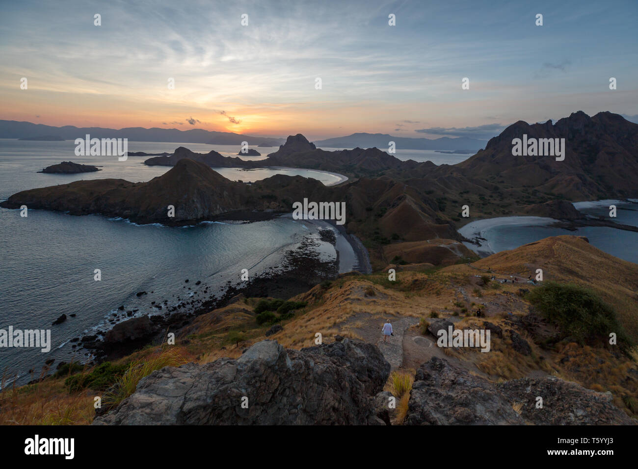 Sunset from hilltop on mountains in Komodo national park silhouettes multiple rock outcrops off shore as sun disappears from view - Stock Image