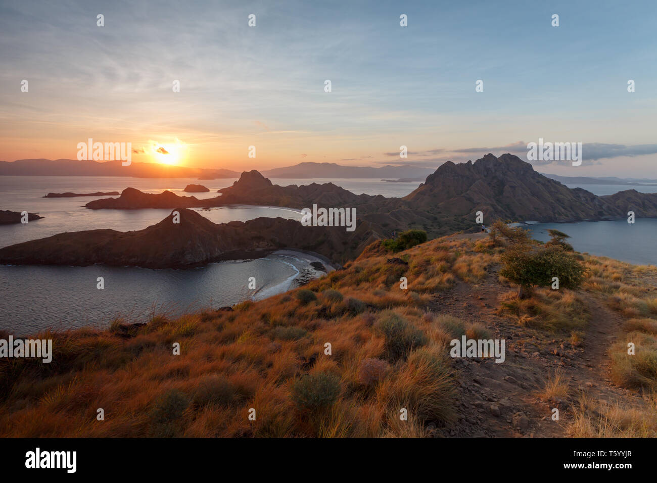 Sunset from hilltop on mountains in Komodo national park silhouettes multiple rock outcrops off shore - Stock Image