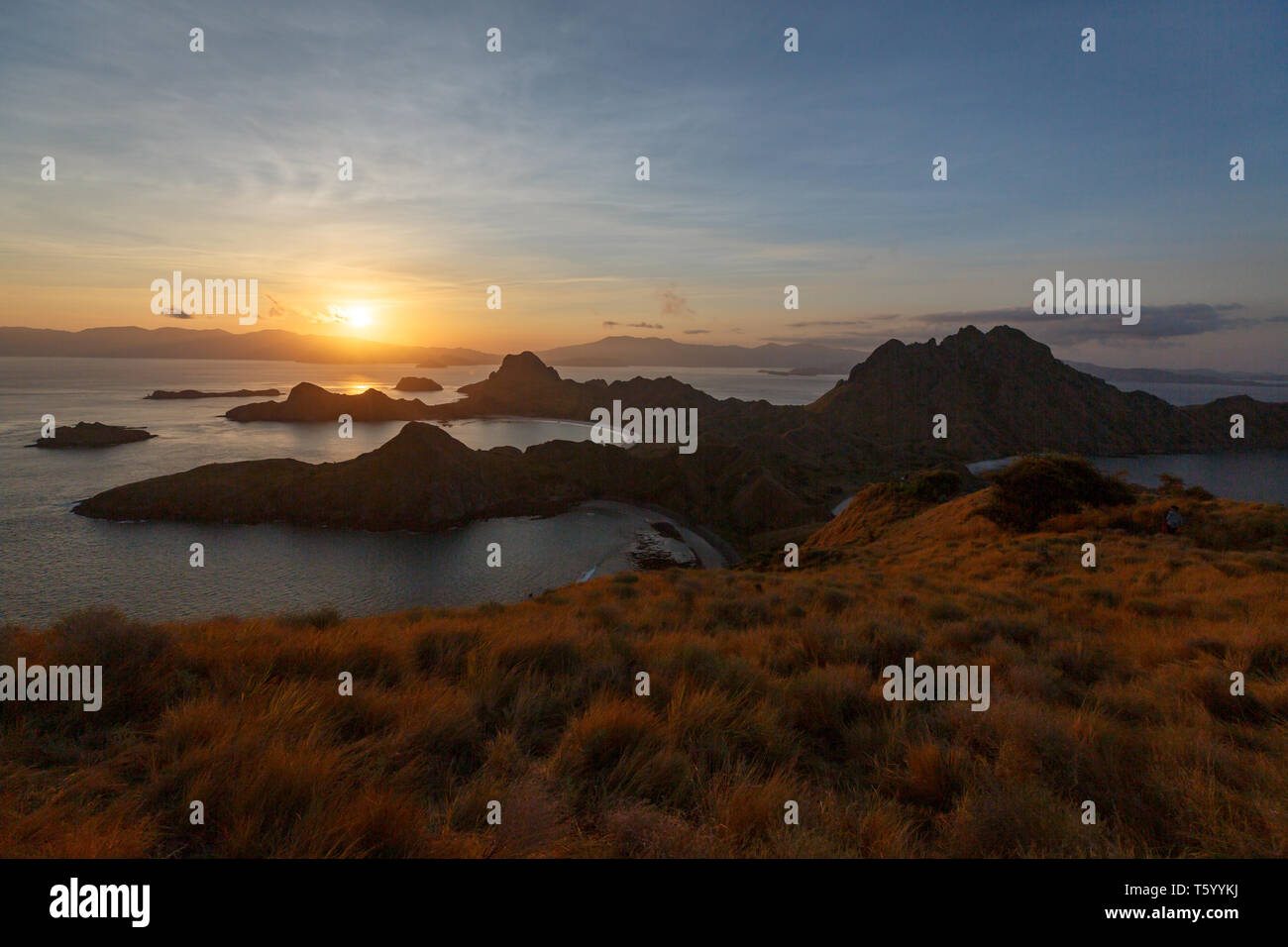 Sunset from hilltop on mountains in Komodo national park silhouettes rock outcrops off shore - Stock Image
