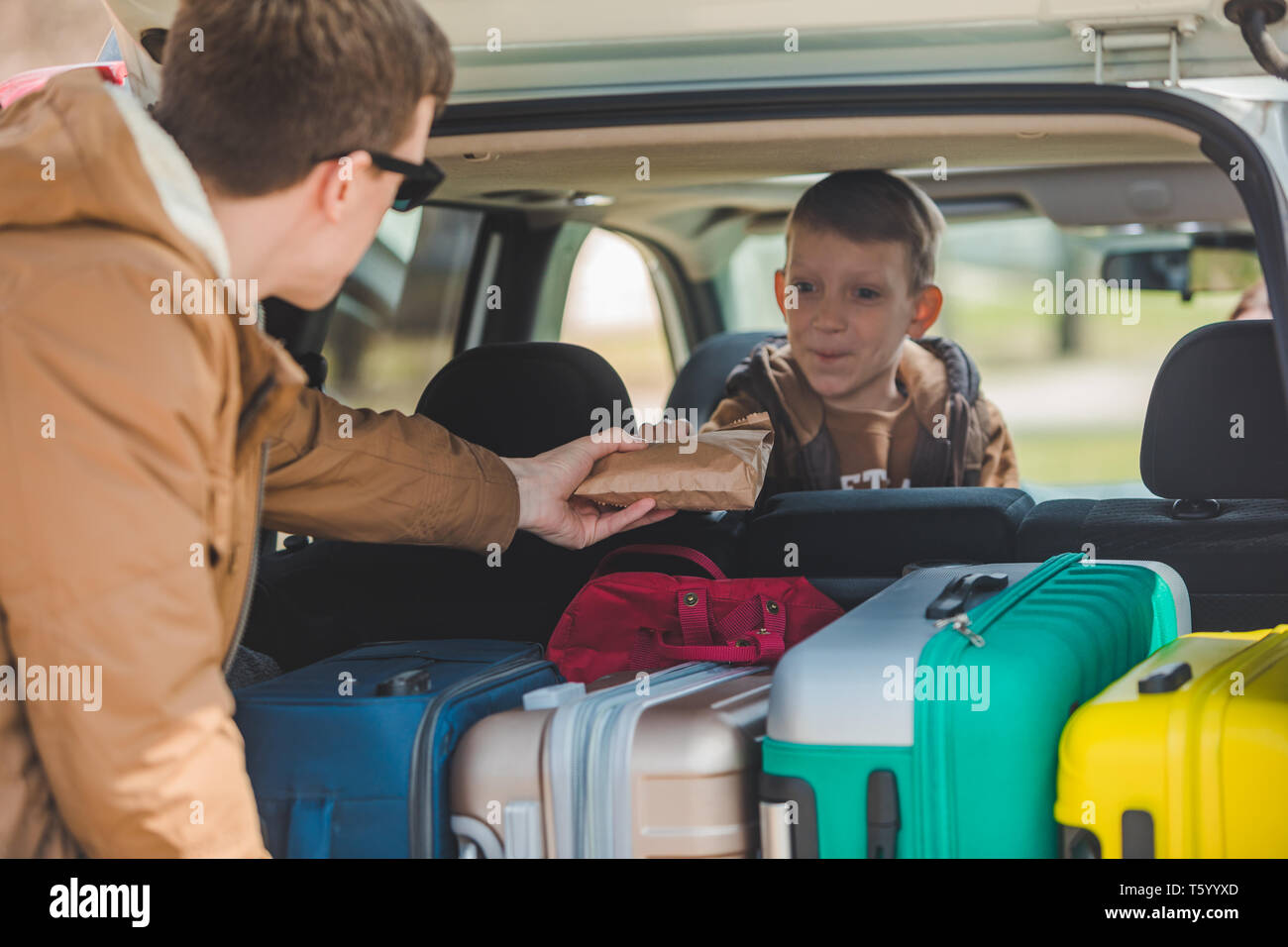 father with son packing bags to car trunk. car travel concept. adventure time - Stock Image