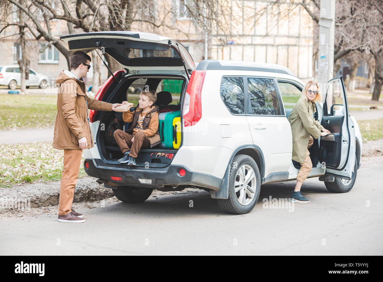 young family packing for car travel. putting bags into trunk. road trip - Stock Image