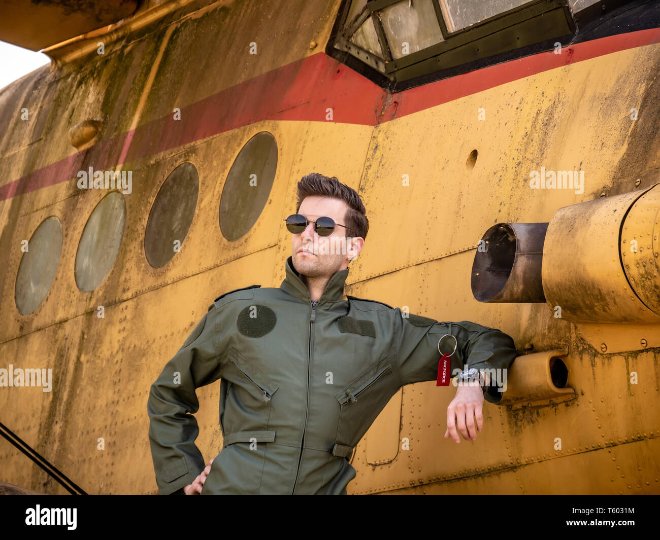 A handsome young man pilot in a green overall standing next to an old plane on a sunny day. Stock Photo