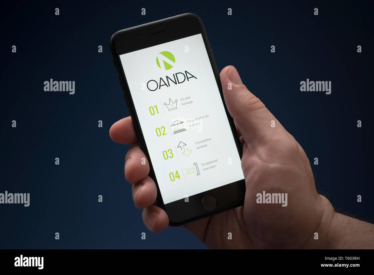 A man looks at his iPhone which displays the Oanda logo