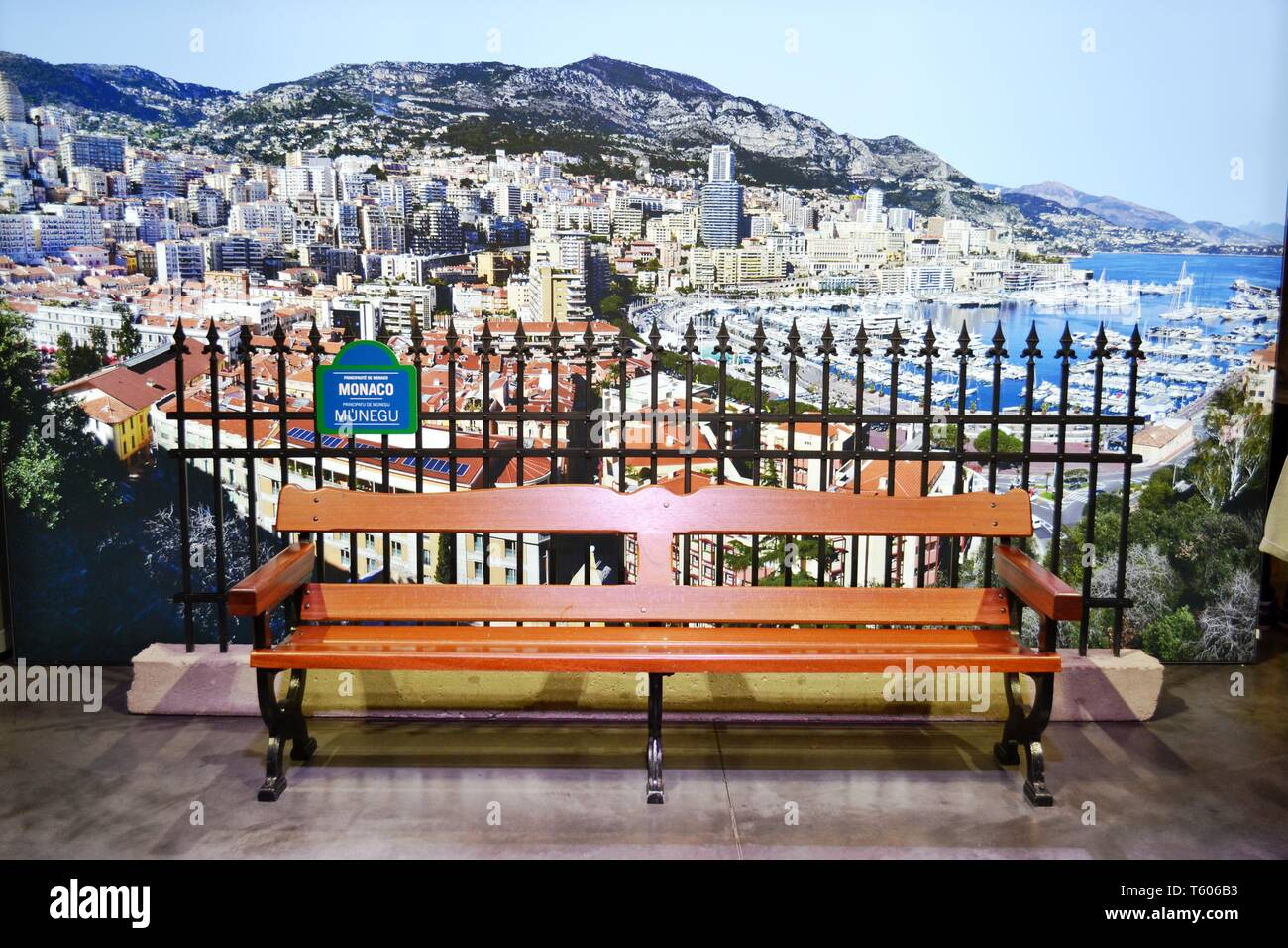 Milan/Italy - October 5, 2015 - Close-up view to a brown wooden bench and a large panoramic city photo at the Monaco pavilion of the EXPO Milano 2015. - Stock Image