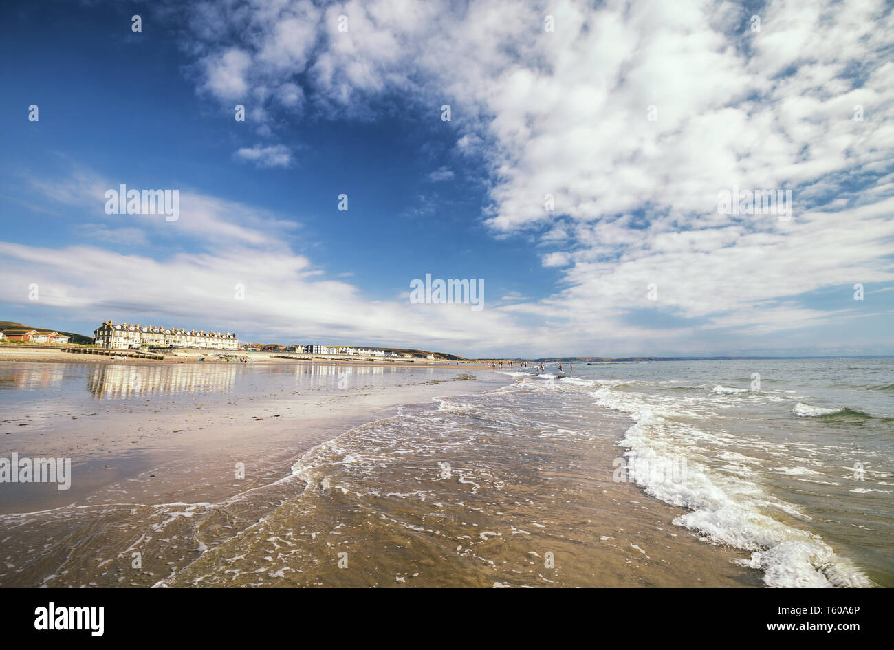 Sea waves washing onto scenic beach at bright summer day. Tywyn in Mid Wales, United Kingdom - Stock Image