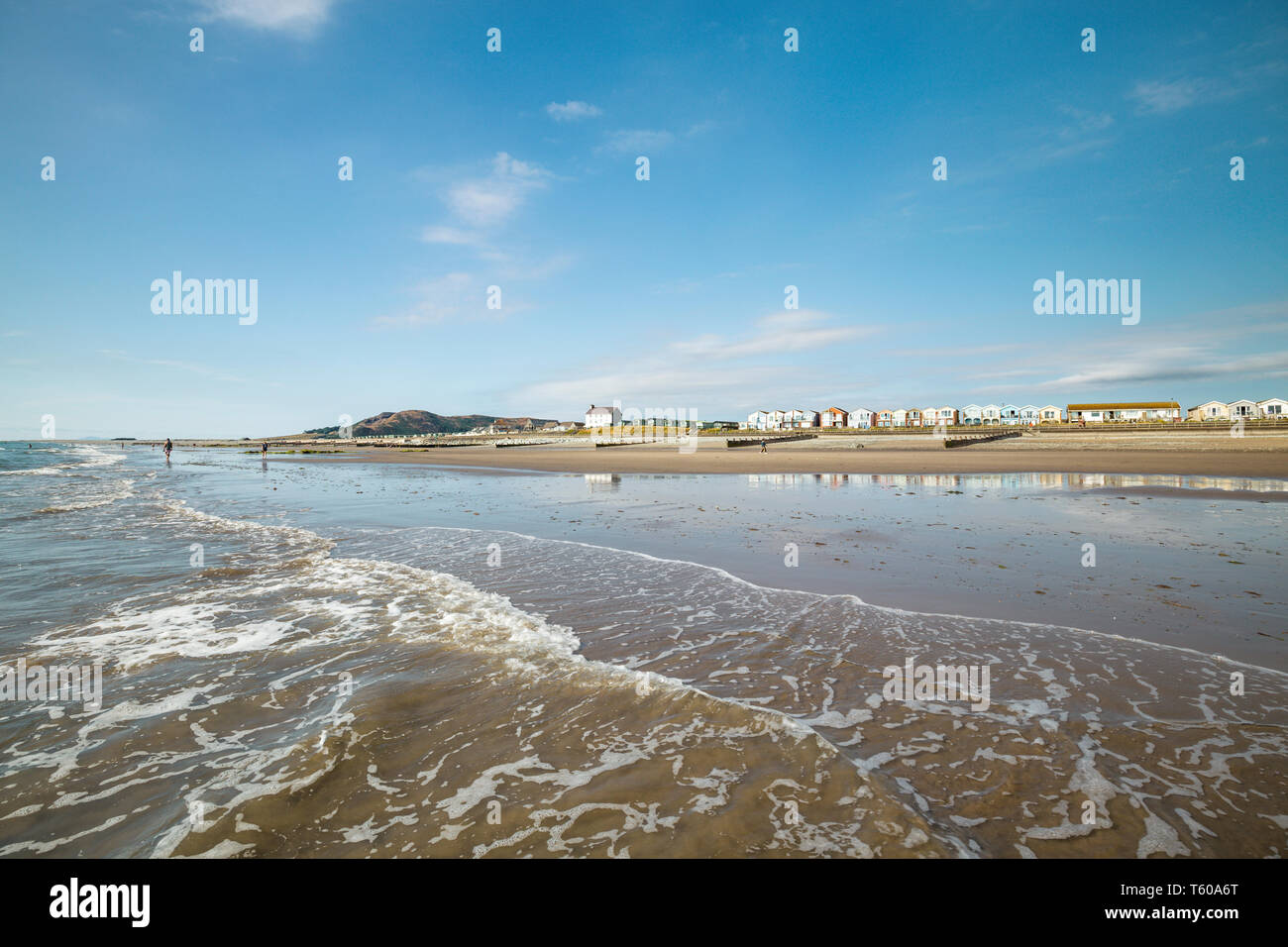 Sea waves washing onto scenic shore of Tywyn in Mid Wales, United Kingdom - Stock Image