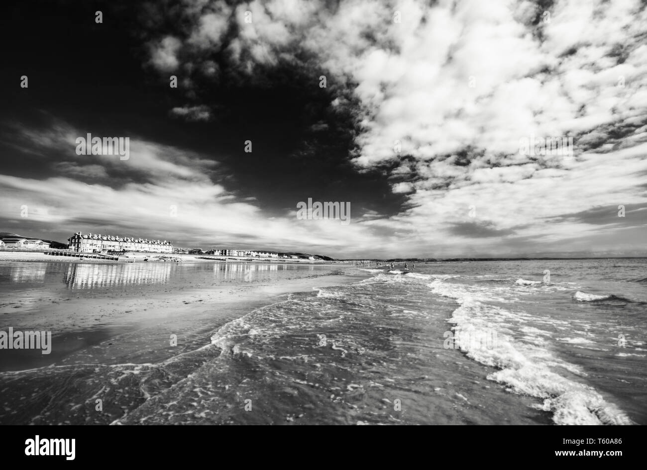 Sea waves washing onto scenic beach at bright summer day. Tywyn in Mid Wales, United Kingdom. Monochrome edit - Stock Image