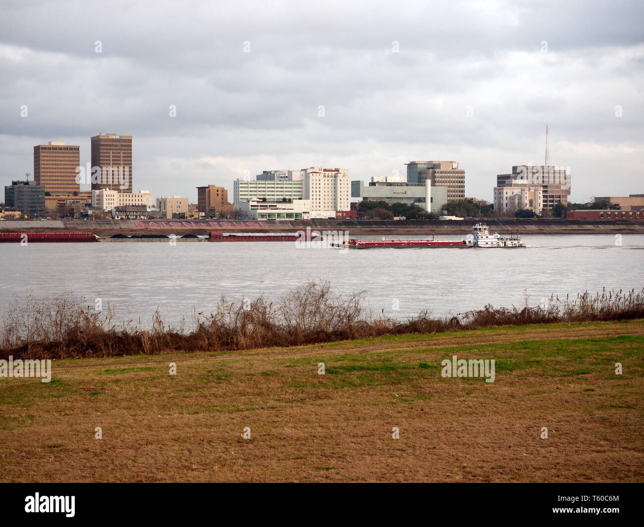 Port Allen, Louisiana, USA - 2019: Downtown Baton Rouge is seen from across the Mississippi River as a towboat  travels upstream. - Stock Image