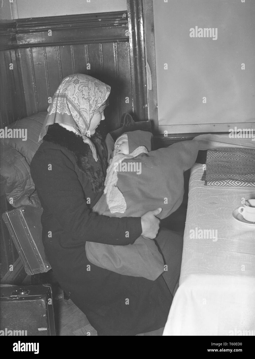 The Winter War. A military conflict between the Soviet union and Finland. It began with a Soviet invasion on november 1939 when Soviet infantery crossed the border on the Karelian Isthmus. A young mother and her baby waiting at the train station in Helsinki to be evacuated from the city.  January 1940. Photo Kristoffersson ref 98-13 - Stock Image