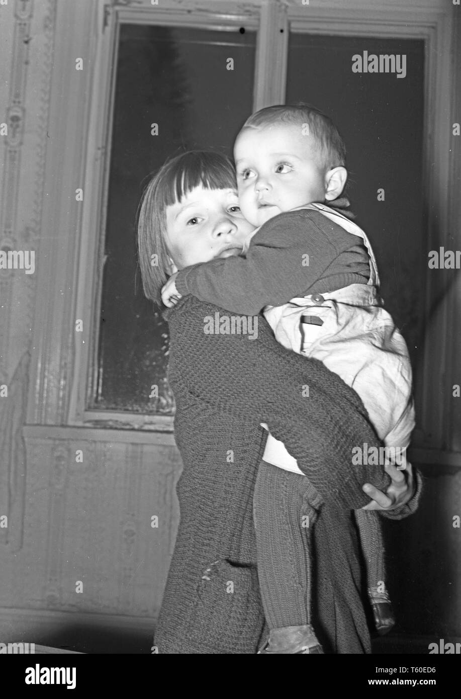 The Winter War. A military conflict between the Soviet union and Finland. It began with a Soviet invasion on november 1939 when Soviet infantery crossed the border on the Karelian Isthmus. Here at Karelian Isthmus Finland  Finnish civilians evacuated from the frontline. A young girl holding her little brother in her arms. December 1939. Photo Kristoffersson ref 98-20 - Stock Image