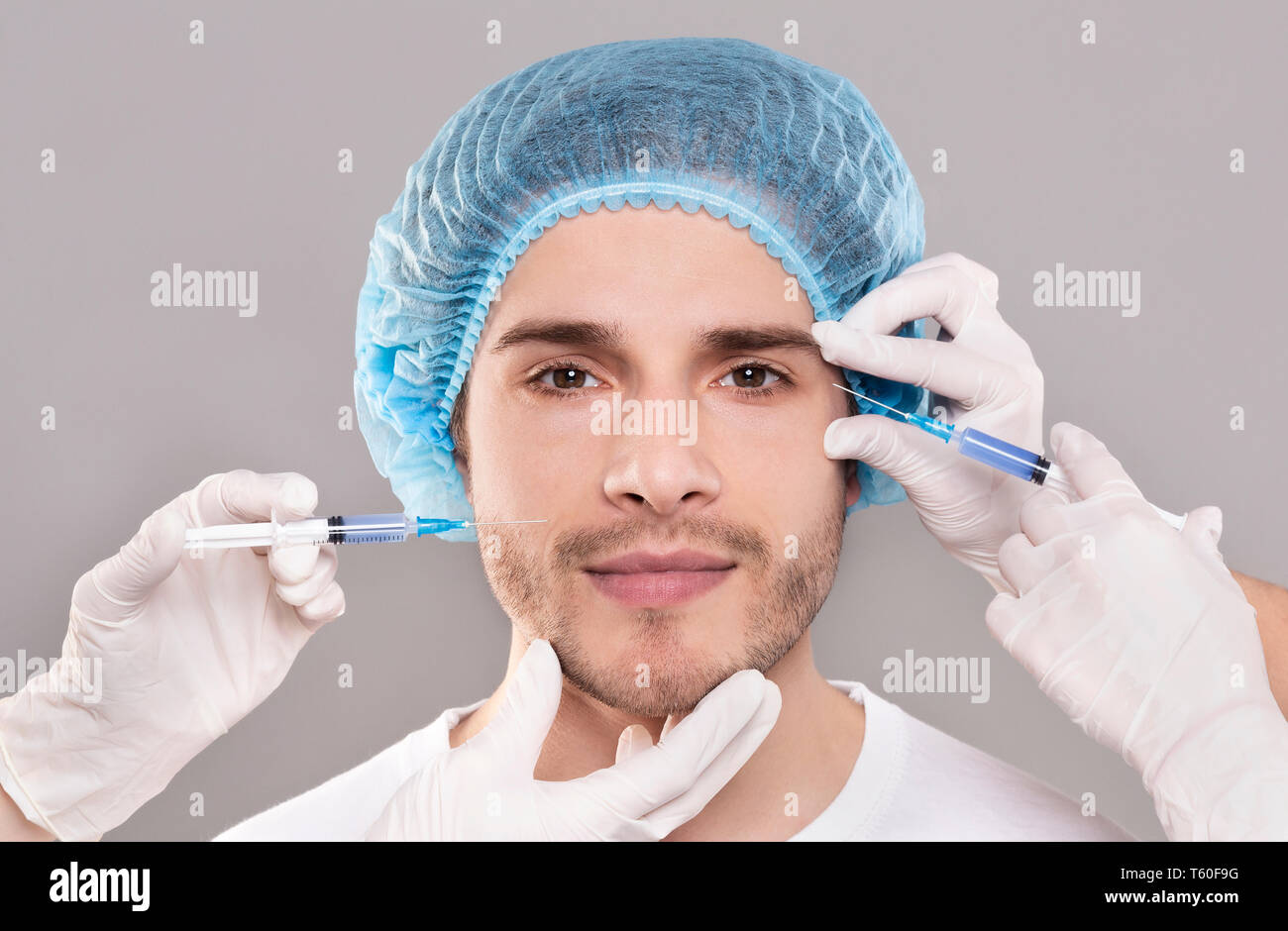 Man's face and beautician's hands with syringes making beauty injections - Stock Image