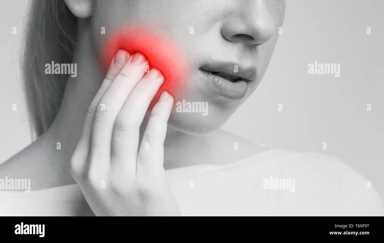 Young woman feeling toothache touching her cheek - Stock Image
