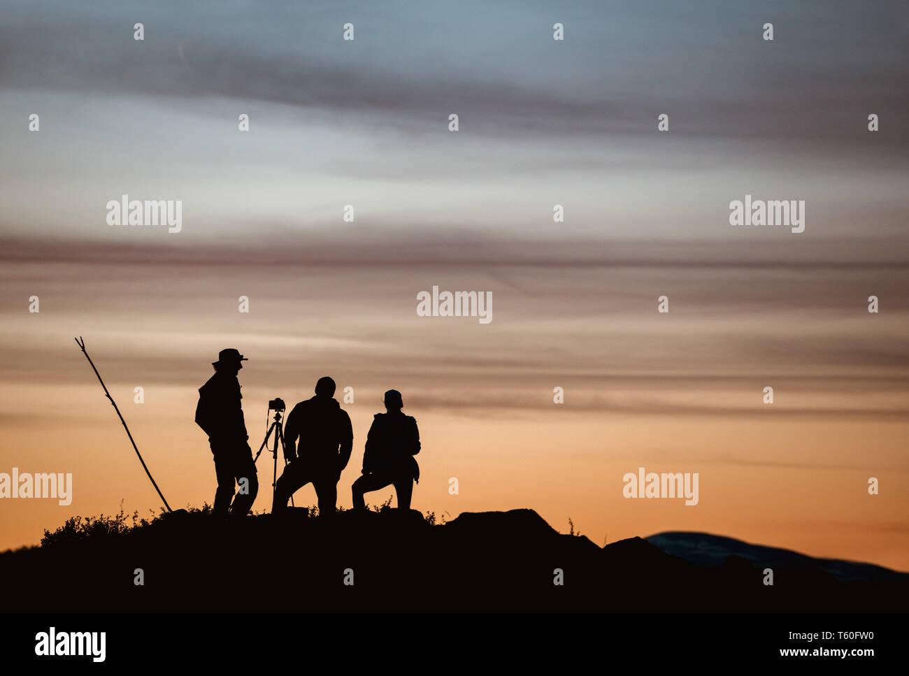 Group of three photographers taking photo against sunset sky Stock Photo