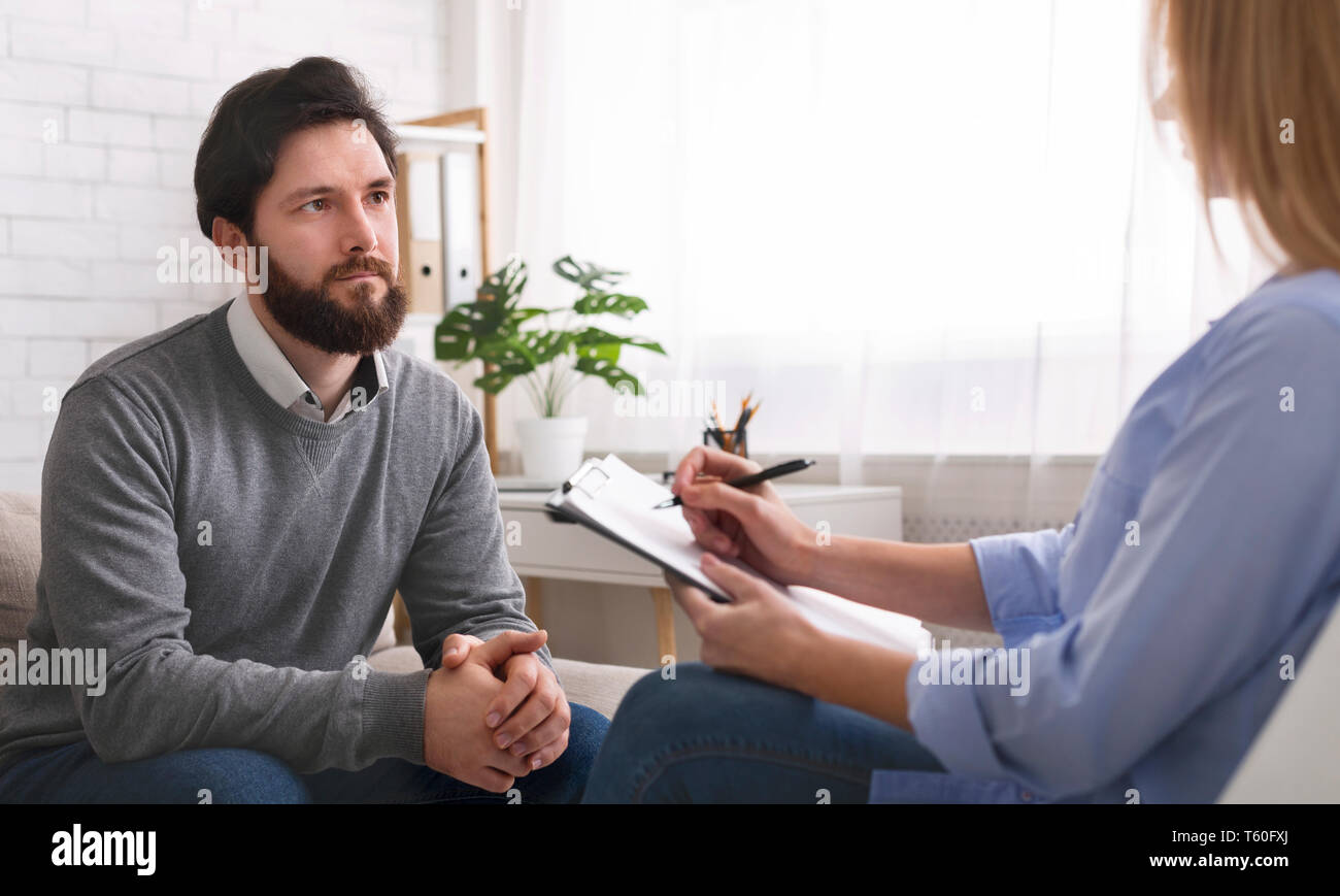 Millennial man talking to specialist at therapy session - Stock Image